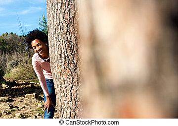 sorridente, giovane, donna africana, levarsi piedi dietro, uno, albero
