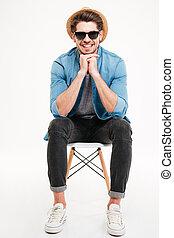 sorridente, giovane, in, cappello, e, occhiali da sole, sedendo sedia