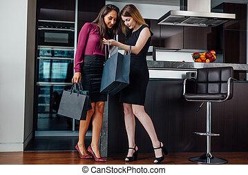 sorridente, giovani donne, il portare, formale, elegante, vestiti, guardando, sacchetto spesa, standing, in, il, moderno, appartamento