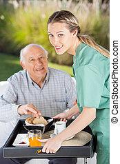 sorridente, servire, femmina, infermiera, ritratto, colazione, uomo senior