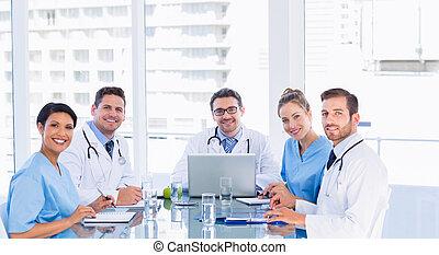sorridente, squadra medica, intorno, scrivania, in, ufficio