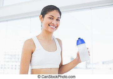 sorrindo, ajustar, mulher, com, garrafa água, em, condicão física, estúdio