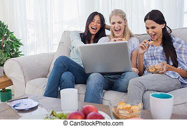 sorrindo, amigos, olhar, laptop, junto, e, comer, biscoitos