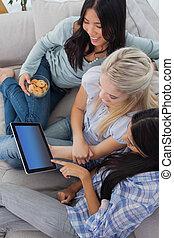 sorrindo, amigos, usando, tablete digital, junto, e, comer, biscoitos, casa, sofá