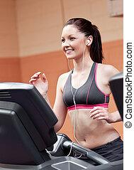 sorrindo, atlético, mulher, treinamento, ligado, um, máquina corrente, com, fones ouvido, em, um, centro aptidão