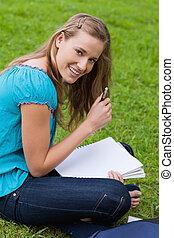 sorrindo, atraente, menina, segurando, dela, caneta, enquanto, olhar, direito, em, a, câmera