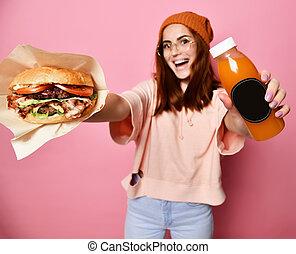 sorrindo, bonito, jovem, loura, mulher, modelo, em, hipster, hoodie, pano, segurando, hamburger, e, garrafa, suco