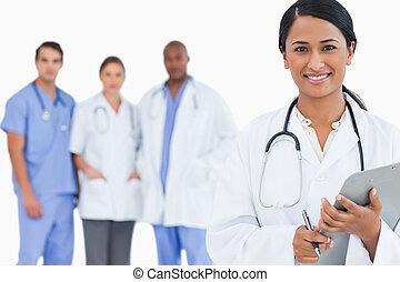 sorrindo, doutor, com, área de transferência, e, membros pessoal, atrás de, dela