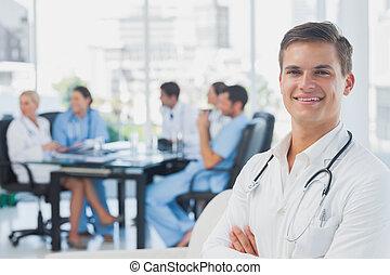 sorrindo, doutor, com, braços dobraram, ficar