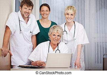 sorrindo, doutores, com, laptop, escrivaninha, em, hospitalar