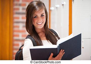 sorrindo, estudante, segurando um livro