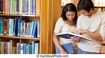 sorrindo, estudantes, olhando um livro