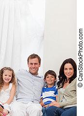 sorrindo, família, sentar-se sofa, junto