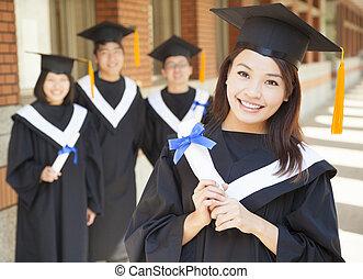 sorrindo, graduado faculdade, segurando, diploma, com, colegas