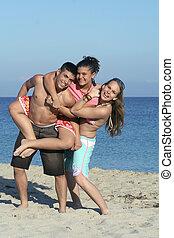 sorrindo, grupo, de, juventude, crianças, adolescentes, tocando, piggyback, ligado, praia, feriado verão