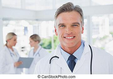 sorrindo, haired cinzento, doutor, ficar, em, seu, escritório