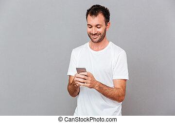 sorrindo, homem jovem, em, camisa branca, usando, smartphone