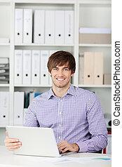 sorrindo, homem negócios, usando computador portátil, em, escritório