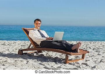 sorrindo, jovem, homem negócios, mentindo, ligado, um convés, cadeira, com, seu, laptop