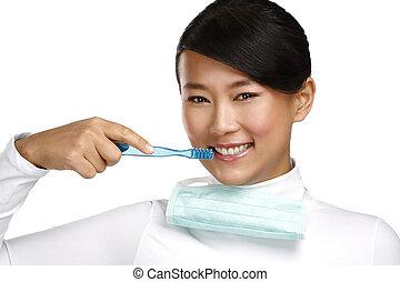 sorrindo, jovem, mulher asian, odontólogo, mostrando, um, escova de dentes
