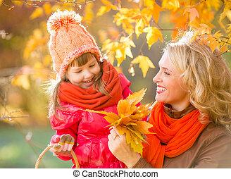 sorrindo, mãe, e, criança, ao ar livre, com, outono, amarelo sai