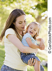 sorrindo, mãe, filha, segurando, ao ar livre