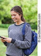 sorrindo, menina jovem, enviando, um, texto, com, dela, telefone móvel