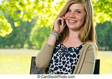 sorrindo, menina jovem, usando, dela, telefone móvel