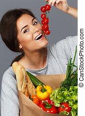 sorrindo, morena, mulher, com, saco mantimento, cheio, de, legumes frescos, e, tomates cereja