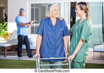 sorrindo, mulher inválida, e, enfermeira, olhando um ao...