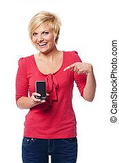 sorrindo, mulher jovem, apontar, tela, de, telefone móvel