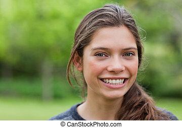 sorrindo, mulher jovem, olhando câmera, enquanto, ficar, em, um, pa