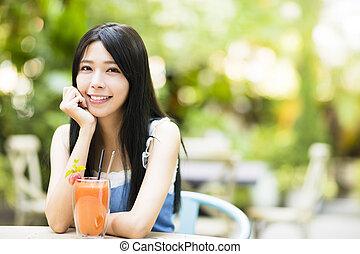 sorrindo, mulher jovem, sentando, em, restaurante