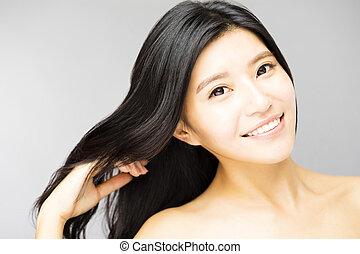 sorrindo, mulher jovem, tocar, longo, e, saudável, cabelo preto