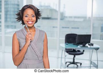 sorrindo, mulher negócios fica, em, dela, escritório, caneta segurando