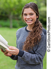 sorrindo, olhando jovem, enquanto, câmera, leitura menina, livro