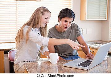 sorrindo, par, comendo café, enquanto, usando, um, laptop