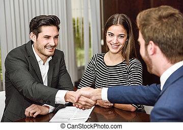 sorrindo, par jovem, apertar mão, com, um, agente de seguros