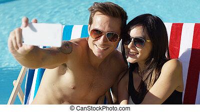 sorrindo, par jovem, levando, um, férias, selfie