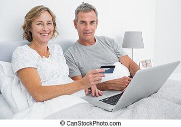 sorrindo, par, usando, seu, laptop, comprar, online