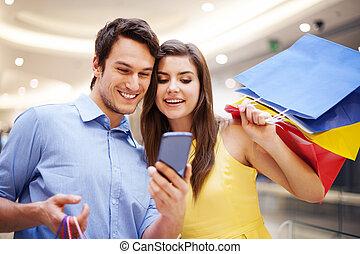 sorrindo, par, verificar, algo, ligado, a, telefone móvel