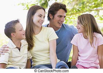sorrindo, sentando, família, ao ar livre