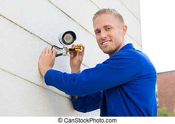 sorrindo, técnico, instalar, câmera, ligado, parede