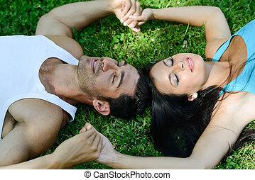 sorrir feliz, par, deitando, ligado, grama verde