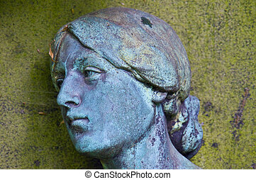old statue of a grieving woman on a cemetery