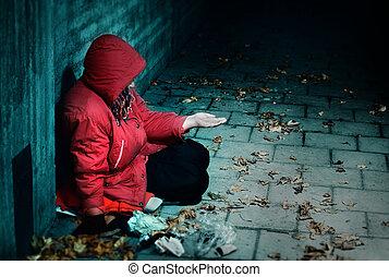 Sorrow - A woman sitting against a brick building