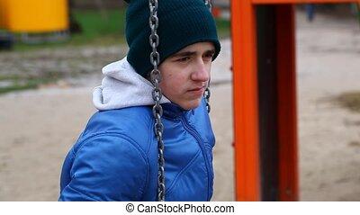 Sorrowful teenage boy swinging in the park episode 1