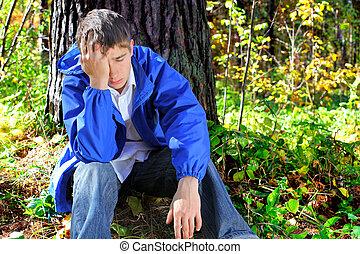 sorrowful young man - sorrowful teenager sitting in the...