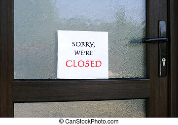 SORRY, WE'RE CLOSED sign on the front door of a little store