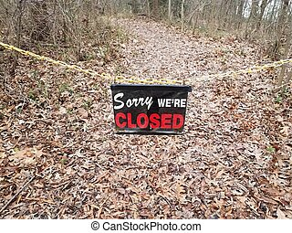 sorry we're closed sign and yellow chain on trail or path